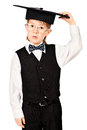 Academic look portrait of thoughtful schoolboy in a suit and hat education isolated over white Stock Photo