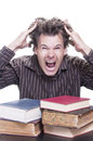 Academic stress young male caucasian student reacts shockingly pulling out his hair with pile of books before him on white Royalty Free Stock Image