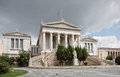 Academy of athens greece the curved stairway statue and flag wide photo showing pillars and clouds Royalty Free Stock Images