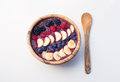 Acai berry smoothie in a wooden bowl topped with bananas, blueberries, raspberries and blackberries Royalty Free Stock Photo