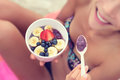 Acai bowl girl eating healthy food on beach woman enjoying bowls made from berries and fruits outdoors for Stock Images