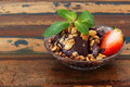 Acai pulp in glass with strawberry muesli and fresh mint on woo brazilian dessert wooden table selective focus copy space Royalty Free Stock Photography