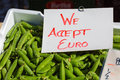 We accept euro a sign on top of box with green peas Stock Photo