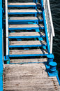 Access stairs to wooden pier with bollards at marina Royalty Free Stock Images