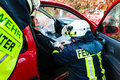 Accident fire brigade rescues victim of a car crash firefighter gives first aid Stock Photo