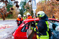 Accident fire brigade rescues victim of a car crash using hydraulic rescue tool and giving first aid infusion Royalty Free Stock Photo