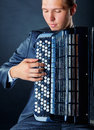 Accordion musician playing the against a black background Stock Photos