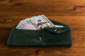 Accumulation a lot of dollars in the green purse on table Royalty Free Stock Photos