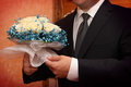 Accurate groom touches tenderly wedding bouquet Stock Photos