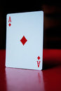 Ace of diamonds card standing upright on red Royalty Free Stock Photography