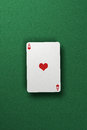 Ace of hearts single floating above green felt surface Royalty Free Stock Images