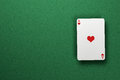 Ace of hearts single floating above green felt surface Royalty Free Stock Photography