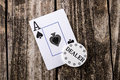 Ace of spades card on wood from a deck cards laying vintage table background with casino dealer chip old west salon style Stock Image