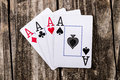 Aces four of a kind poker on vintage wood table old west salon style Stock Photography