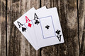 Aces three of a kind poker on vintage wood table old west salon style Stock Photo