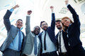 Achievers ecstatic business partners in suits raising their arms and expressing triumph Royalty Free Stock Images