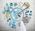 Achieving a goal hand drawing target on the concrete wall surrounded by pictures of money rocket charts cogwheels and puzzles Stock Photo