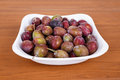 Acid purple and green plums blackthorns in bowl on wooden desk Stock Images
