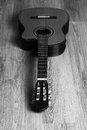 Acoustic classic guitar on a wooden floor black and white image of Stock Images