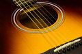 Acoustic guitar closeup with sunburst finish a showing sound hole rosette strings frets neck bridge and bridgepins Royalty Free Stock Image