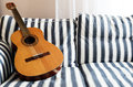 Acoustic guitar on a couch striped horizontal Royalty Free Stock Photos