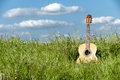 Acoustic guitar in the grass field with white clouds on blue sky background Royalty Free Stock Images