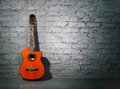 Acoustic guitar leaning on grungy wall Stock Photography