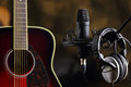 Acoustic guitar, microphone and earphones Royalty Free Stock Photo
