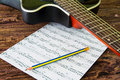 Acoustic guitar and sheet musical notes on the table. Royalty Free Stock Photo