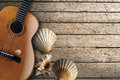 Acoustic guitar on wooden boardwalk brown with four sea shells beach floor over summer sand Stock Photos
