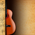 Acoustic guitar on yellow stained paper brown with and brown and musical notes blurred Royalty Free Stock Photo