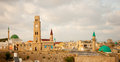 Acre rooftop view of the old city of at sunset with the clock tower minarets of sinan basha mosque and al jazzar mosque and other Royalty Free Stock Photo