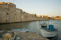 Acre sea wall fishing nets and boats and the old in the old city of israel Stock Photos
