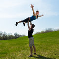 Acrobatic balance young men holds in his hand a young women who does Stock Photo