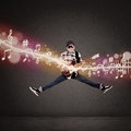 Acrobatic guitarist jumping with musical notes on grey background Royalty Free Stock Image