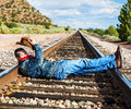 Across train tracks famous cow boy boots and feets Stock Photos