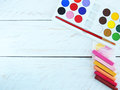 Acrylic paint set and soft and oil pastels styled stock photography with paintbrush on a white wood background Royalty Free Stock Photography