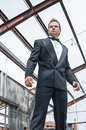 Action hero low angle view of handsome courageous male caucasian man in tuxedo standing boldly in torn down warehouse structure Stock Image