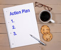 Action plan spiral bound notebook with blue text reading and below it blank spaces marked and beside the notebook is a cup of Stock Images