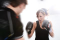 Action shot of girl with personal trainer woman working out on punch bag in gym Stock Photos