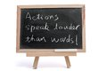 Actions speak louder than words saying written on blackboard over white background Stock Images