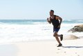 Active african american man running by water on the beach Royalty Free Stock Photo