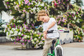 Active blond kid boy and bicycle near the sea. Toddler child dreaming and having fun on warm summer day. outdoors games for childr Royalty Free Stock Photo