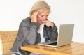 Active blond senior woman with formal clothes sitting thoughtful at a desk in front of a silver laptop Royalty Free Stock Images
