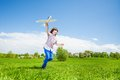 Active boy holding airplane toy during running Royalty Free Stock Photo