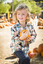 Active boy holding his pumpkin at a pumpkin patch adorable little sitting and in rustic ranch setting the Royalty Free Stock Images