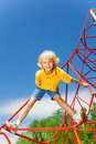 Active boy stands on red rope with legs apart and holds one arm Stock Photo