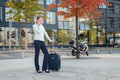 Active business woman ready to travel young talking on mobile phone while waiting outdoor next her trolley case Stock Image