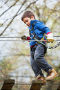 Active child climber walking on steps at height in an adventure park Stock Photos