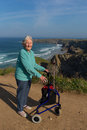 Active elderly lady pensioner in eighties with three wheel mobility frame by beautiful coast scene happy female wheeled and Royalty Free Stock Images